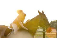 Woman on horseback petting horse in rural pasture Stock Photos