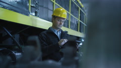Technician in Hard Hat Using Tablet in Industrial Environment Stock Footage