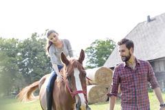 Man leading woman horseback riding in rural pasture Stock Photos