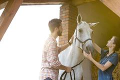 Couple petting horse in rural stable - stock photo