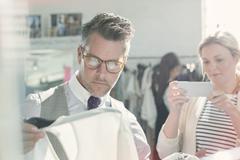 Fashion designers photographing clothing with camera phone Kuvituskuvat
