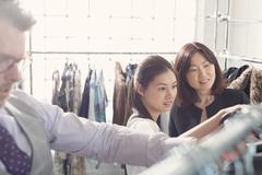 Fashion designers examining clothing on racks - stock photo