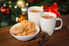 oat cookies and hot chocolate over christmas tree - stock photo