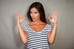Confident woman in blue blouse congratulating with ok sign Stock Photos