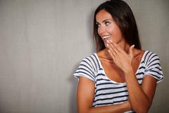 Surprised woman in blue blouse looking away with hand to mouth - copy space - stock photo
