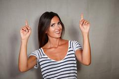 Stock Photo of Happy woman in blue blouse pointing up while looking at camera