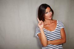 Young caucasian lady in casual clothing standing with finger raised - copy sp Stock Photos