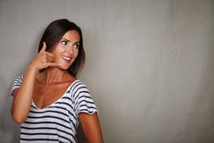Brunette girl in casual clothing gesturing a call while looking away - copy s - stock photo