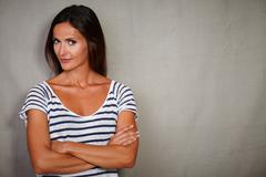Confident woman standing with arms crossed while looking at camera - copy spa - stock photo