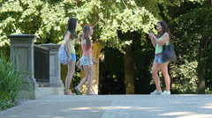 Three girls taking pictures in Lazienki Park, Warsaw Stock Footage