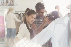Photographer and fashion designer examining clothing - stock photo