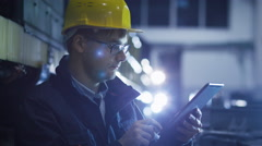 Technician in Glasses and Hard Hat Using Tablet in Industrial Environment Stock Footage