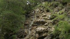 Rill streaming and falling down mossy rocks Tilt Down Stock Footage