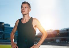 Confident runner on athletics racetrack - stock photo