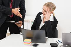 Close-up Of Businessperson Talking To Stressed Employee For Her Mistake In Wo - stock photo