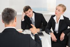 Group Of Three Businesspeople Having Argument At Workplace Stock Photos