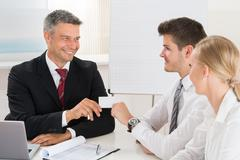 Male Consultant Giving Visiting Card To Young Couple In Office Stock Photos