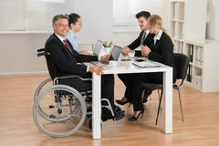 Happy Mature Disabled Businessman Having Meeting With Colleagues In Office Kuvituskuvat