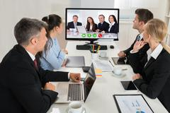 Group Of Businesspeople Watching An Online Presentation On A Desktop Computer Stock Photos