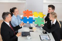 Happy Businesspeople Joining Multicolored Puzzle Piece In Meeting - stock photo