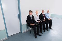 Group Of Applicants Sitting On Chair For Giving Interview In Office - stock photo