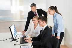 Group Of Businesspeople Looking At Graph On Computer In Office Stock Photos