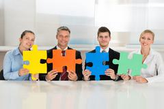 Team Of Businesspeople Holding Four Multi-colored Puzzles At Desk - stock photo