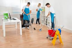 Group Of Three Janitors In Blue Apron Cleaning Office - stock photo