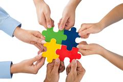 Close-up Of People Hands Holding Jigsaw Pieces Over White Background - stock photo