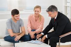 Mature Financial Advisor Showing Graph On Paper To Young Couple Stock Photos