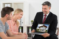 Mature Estate Agent Showing House On Laptop To Young Couple Stock Photos
