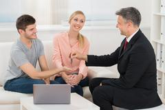 Mature Real Estate Agent Giving House Key To Young Happy Couple - stock photo