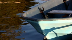 Fall color reflected in water near a small blue boat Stock Footage