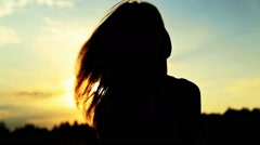 A silhouette of a woman  on a sunset turns her head - stock footage
