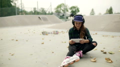 Happy girl wearing rollerblades and listening music in skate park, steadycam sho Stock Footage