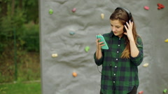 Girl standing againt climbing wall and listening music on headphones Stock Footage