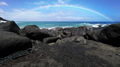 Rainbow over a beach with lava rocks in Hawaii - stock footage