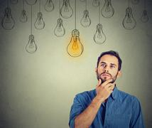 man looking up with idea light bulb above head - stock photo