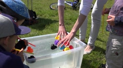 Kids with straw play duck race in plastic water pool. 4K Stock Footage