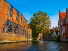 Medieval houses along canals of Bruges in autumn time Stock Photos