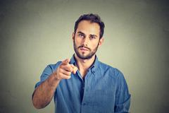 Portrait of a angry young man pointing finger at you camera gesture Stock Photos