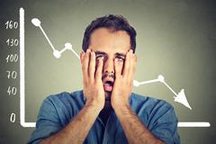 Portrait frustrated stressed young man desperate with financial market chart  - stock photo