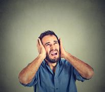 annoyed, stressed man covering his ears, looking up, stop making loud noise - stock photo
