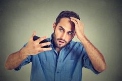 Closeup portrait, shocked man feeling head, surprised he is losing hair, rece - stock photo