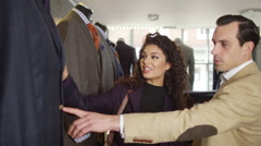 4K Attractive couple shopping for new suit in a man's clothing store - stock footage