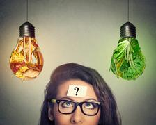Woman thinking looking at junk food and vegetables shaped as light bulb - stock photo