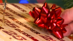 Putting bow on a christmas present under christmas tree HD Stock Footage