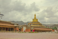 Timelapse Labrang Monastery stupa with prayer wheels and a monk Stock Footage