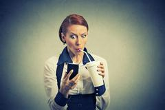 Surprised business woman reading news on smart phone drinking soda coffee Stock Photos
