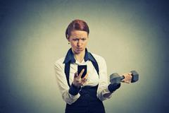 Angry business woman reading news e-mail on mobile phone lifting dumbbell Stock Photos